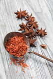 Saffron in spoon with anise on wooden background Royalty Free Stock Photography
