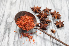 Saffron in spoon with anise on wooden background Stock Images