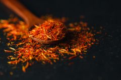 Saffron in a spoon on a dark background, selective focus, macro shot, shallow depth of field Stock Image