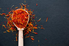 Saffron in a spoon on a dark background, selective focus, macro shot, shallow depth of field Royalty Free Stock Photography