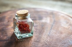 Saffron in the vial. On the wooden board Royalty Free Stock Photos