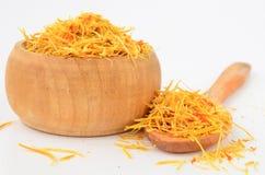 Saffron in wooden bowl. Yellow saffron, tasty and costly spice in wooden bowl and wooden teaspoon isolated on white background stock photo