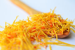 Saffron on wooden teaspoon. Macro shot of Saffron, spice more expensive than gold, on wooden teaspoon on white background Stock Photography