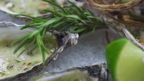 Safood背景 牡蛎烘烤用乳酪、石灰和草本在板材 海鲜盘在海洋餐馆 影视素材