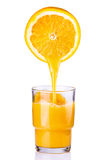 Saft, der in ein Glas der Orange gegossen wird Stockfotografie