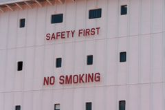 Saftey First, No Smoking Sign. Safety First No Smoking sign on a ship with windows stock photos