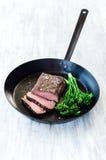Saftig biff på den svarta pannan med nya gröna grönsaker Royaltyfria Foton