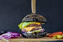 Saftig dubbel ostburgare Sidosikt, svart bakgrund, utrymme f?r text royaltyfri foto
