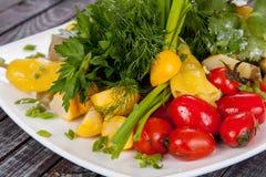 Saftig, för sommargrönsaksallad klipp från nya grönsaker och gräsplaner i en härlig portion på en trätabell royaltyfria foton