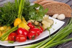 Saftig, för sommargrönsaksallad klipp från nya grönsaker och gräsplaner i en härlig portion på en trätabell royaltyfri fotografi