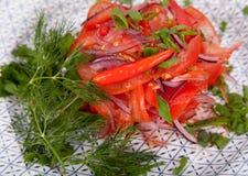 Saftig, för sommargrönsaksallad klipp från nya grönsaker och gräsplaner i en härlig portion på en trätabell royaltyfri bild
