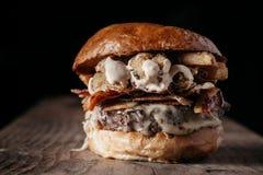 Saftig hamburgare på mörk bakgrund med negativt utrymme Royaltyfria Bilder