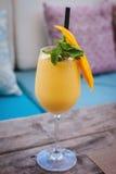 Saftig smoothie från mango i exponeringsglas med sugrör på trätabellen royaltyfria foton