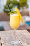 Saftig smoothie från mango i exponeringsglas med sugrör på trätabellen royaltyfria bilder