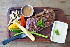 Saftig stek med den kokta grönsaken på träplattan Arkivfoto