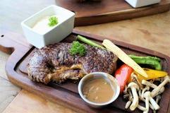 Saftig stek med den kokta grönsaken på träplattan Royaltyfria Bilder