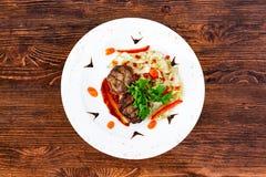 Saftig stekskyddsling från medelsällsynt nötkött med en sås på en vit platta arkivfoton