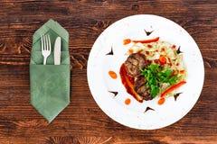 Saftig stekskyddsling från medelsällsynt nötkött med en sås på en vit platta med anordningar royaltyfri fotografi