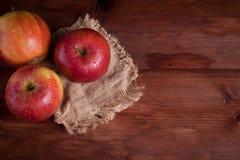 Saftiga äpplen på ett wood skrivbord Arkivfoton
