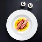 Saftiga delar av grillad filébiff tjänade som med tomater, sau Fotografering för Bildbyråer