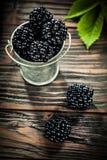 Saftiga dewberries i metall ösregnar på tappningträbräde royaltyfria foton