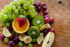 Saftiga frukter på ett träbräde Fotografering för Bildbyråer