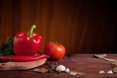 Saftiga grönsaker, örter och kryddor på mörkt trä Royaltyfria Bilder