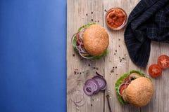 Saftiga hemlagade hamburgare med sesamfrö, tomatsås, peppar och havet som är salta på träbräde över blå bakgrund Utrymme för text Royaltyfria Bilder