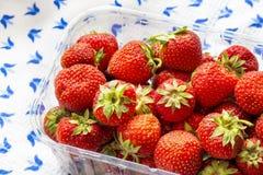 Saftiga jordgubbar på en dillandebordduk arkivbilder