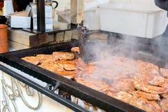 Saftiga köttbiffar som grillar på grillfest under press för tappningjärngaller på gatamatfestivalen royaltyfria bilder
