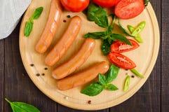 Saftiga korvar med tomater och basilika på en rund skärbräda på en mörk träbakgrund Royaltyfria Foton