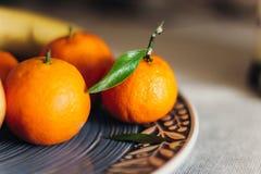 Saftiga mandariner på blåttplattan lantlig jultabell med utrymme Fotografering för Bildbyråer