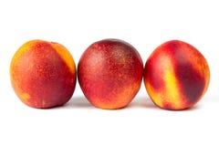 Saftiga mogna persikor på den vita bakgrunden i makro Royaltyfri Foto