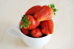 Saftiga nya röda jordgubbar i en vit kopp Arkivbild