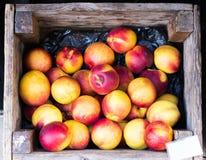 Saftiga persikor i träask Arkivfoto