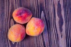 Saftiga persikor på träbakgrund Fotografering för Bildbyråer