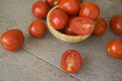 Saftiga tomater på grå bakgrund Royaltyfria Bilder