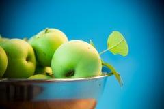 Saftige Äpfel grünen in einer Schüssel auf einem Blau Lizenzfreie Stockbilder