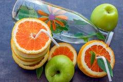 Saftige Äpfel und Orangen mit Rohren für ein Cocktail Flasche mit Stockbild