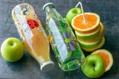 Saftige Äpfel und Orangen mit Rohren für ein Cocktail Flaschen mit Lizenzfreie Stockfotos