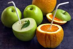 Saftige Äpfel und Orangen mit Rohren für ein Cocktail Trinken Sie das ju Stockfotos