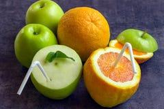 Saftige Äpfel und Orangen mit Rohren für ein Cocktail Trinken Sie das ju Lizenzfreie Stockfotografie