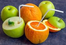 Saftige Äpfel und Orangen mit Rohren für ein Cocktail Trinken Sie das ju Lizenzfreie Stockfotos