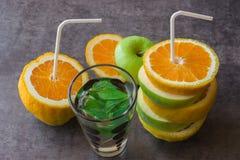 Saftige Äpfel und Orangen mit Rohren für ein Cocktail Trinken Sie das ju Lizenzfreies Stockfoto