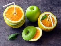 Saftige Äpfel und Orangen mit Rohren für ein Cocktail Trinken Sie das ju Lizenzfreies Stockbild
