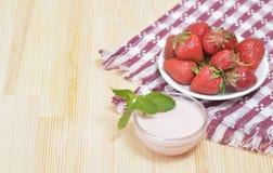 Saftige Erdbeere auf einer Platte auf einem Holztisch Lizenzfreie Stockfotos