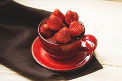 Saftige Erdbeere in der roten Schale auf einer dunklen Tischdecke Stockfotografie