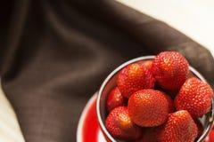 Saftige Erdbeere in der roten Schale auf einer dunklen Tischdeckennahaufnahme Lizenzfreie Stockfotografie
