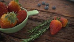 Saftige frische Erdbeeren in einer weißen Schüssel auf einem weißen hölzernen Hintergrund stock footage