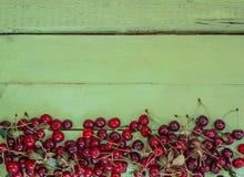 Saftige frische Kirschen auf einem hellen hölzernen Hintergrund Stockbild